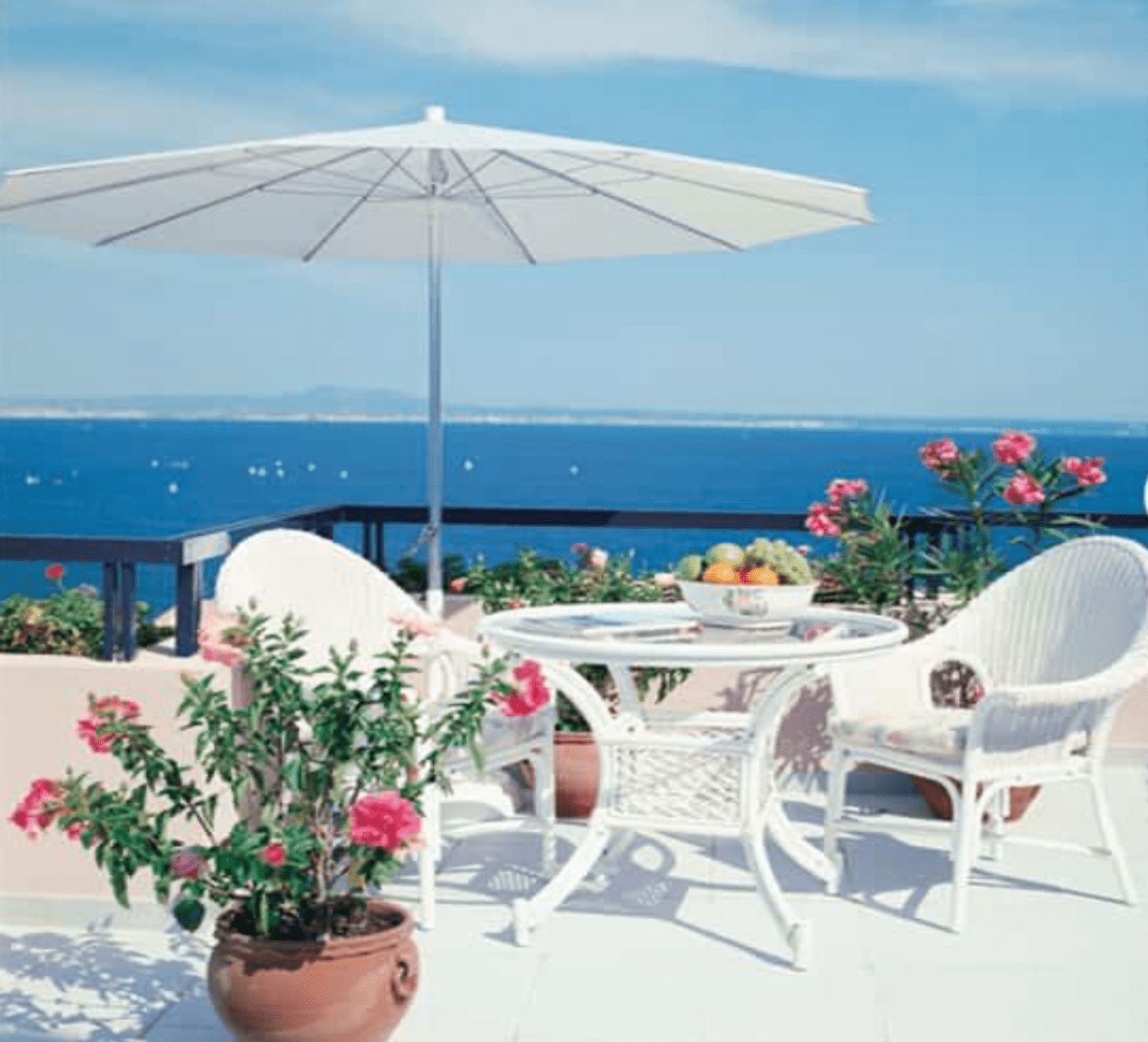 white outdoor table for two with umbrella with an ocean view