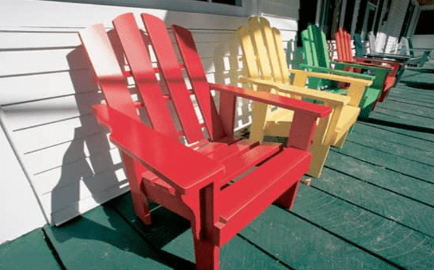 red chair and yellow chair and other multi colored chairs on green porch and white house
